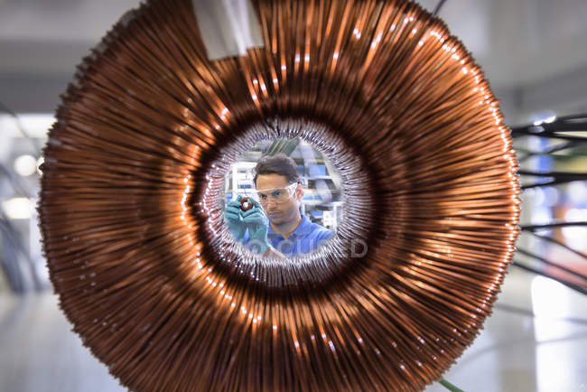 Worker inspecting electromagnetic coil seen through large coil in electromagnetics factory — Stock Photo