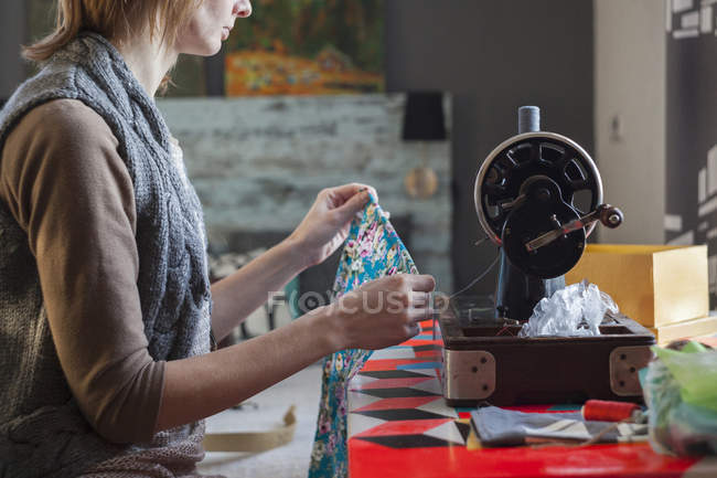 Woman with vintage sewing machine inspecting fabric at table — Stock Photo