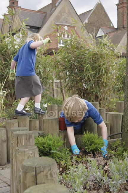 Escola menino e menina plantando vegetação no jardim — Fotografia de Stock