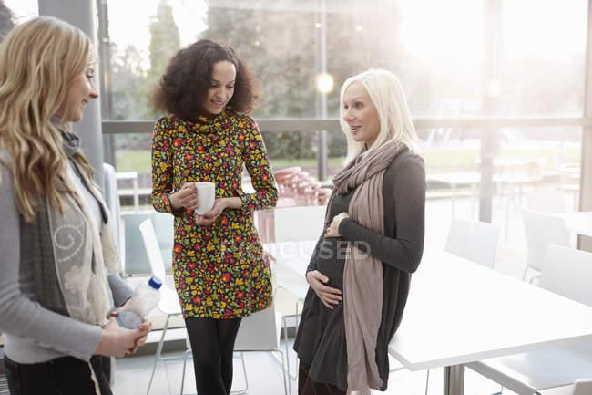 Embarazada mujer de negocios charlando con colegas en el cargo - foto de stock