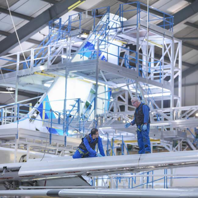 Ingenieros trabajando en ala de aeronaves en fábrica de mantenimiento de aeronaves - foto de stock