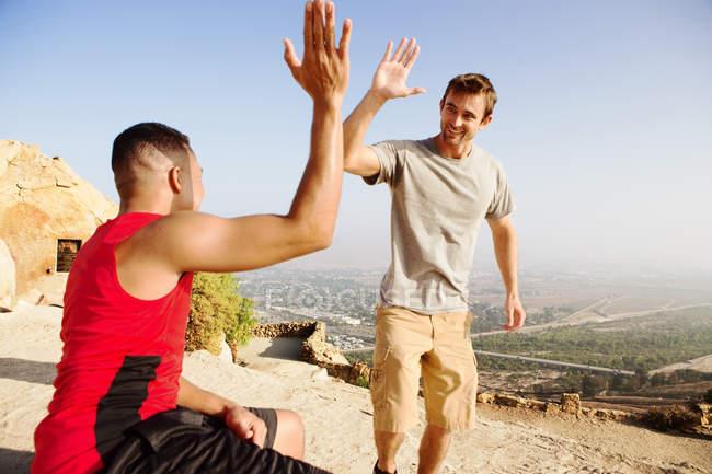 Два друга-мужчины, на вершине горы, дают пять — стоковое фото