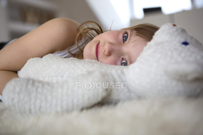 Girl lying on furry bed with teddy bear — Stock Photo