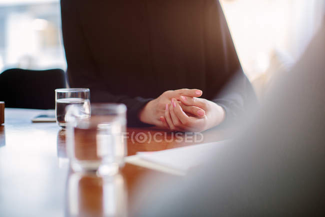 Cropped close up of mature businesswoman interviewing candidate at boardroom table — Stock Photo