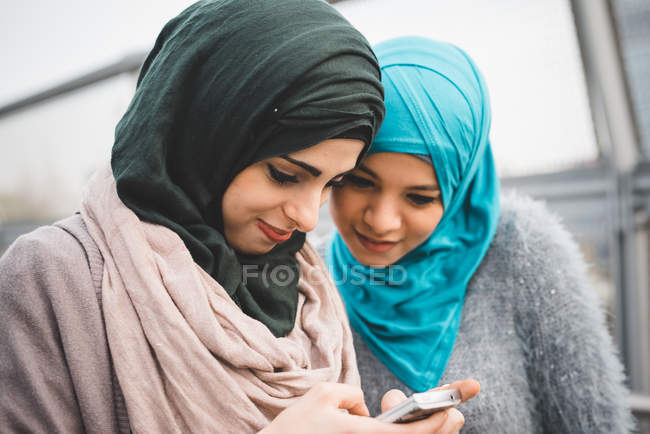Two young female friends reading smartphone texts on park path — Stock Photo