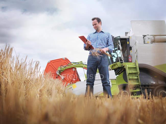 Agricoltore che controlla le colture in azienda — Foto stock