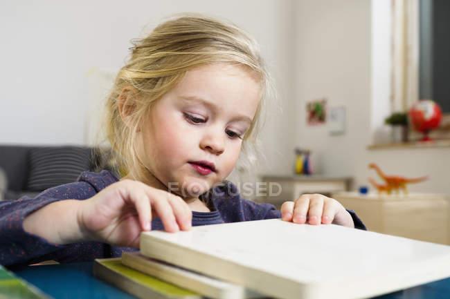 Chica arreglando bloques cuadrados en la mesa - foto de stock