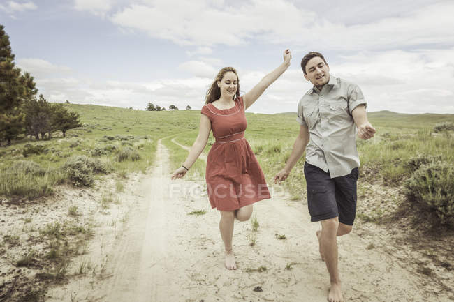 Happy young couple running barefoot along sandy track, Cody, Wyoming, USA — Stock Photo