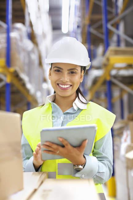 Mujer joven con tableta digital en almacén de distribución - foto de stock