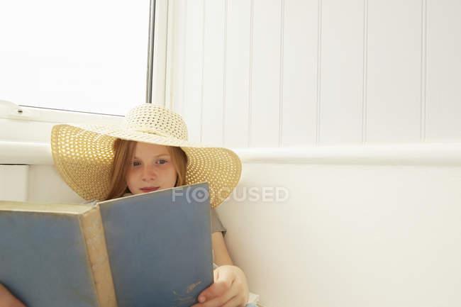 Девушка в зонтике читает на крыльце — стоковое фото