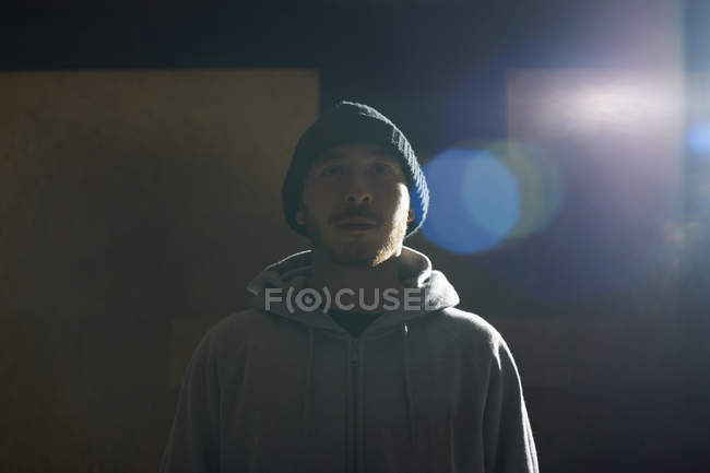 Portrait of young man wearing knit hat and hooded top — Stock Photo
