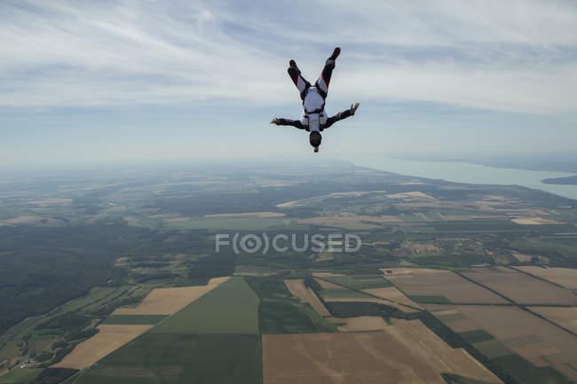 Hombre paracaidista volando boca abajo por encima de Siofok, Somogy, Hungría - foto de stock