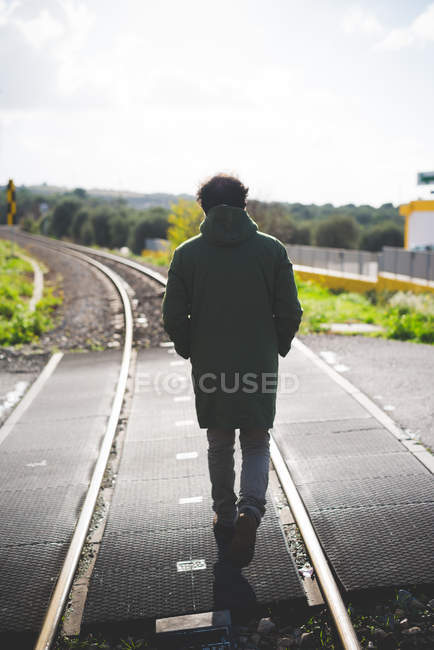 Rear view of mid adult man standing on railway crossing — Stock Photo