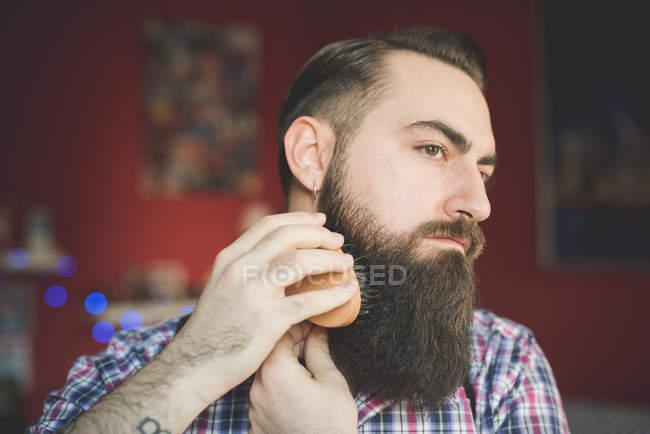 Jovem barbudo escovando sua barba — Fotografia de Stock