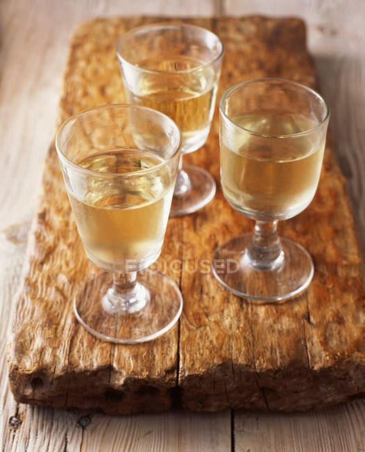 Vasos de vino blanco sobre tabla de cortar de madera - foto de stock