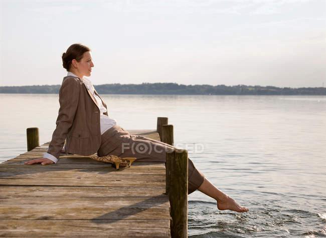 Woman sitting on pier at lake — Stock Photo
