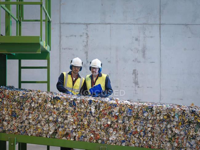 Trabajadores inspeccionando fardos de latas - foto de stock