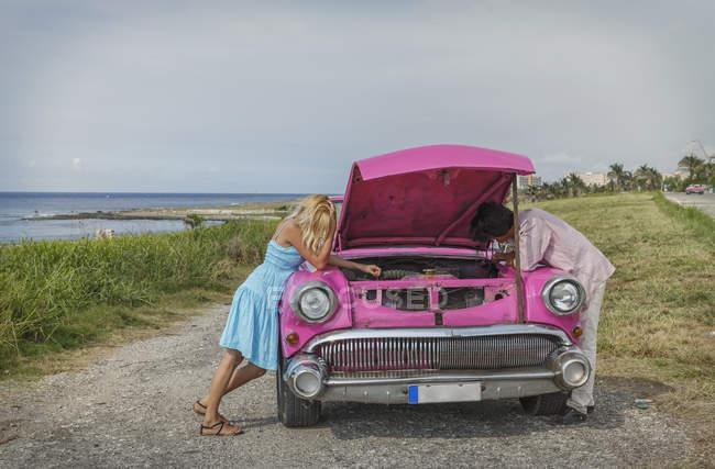Junges paar versucht, ein Oldtimer Cabrio fix an Küste, Havanna, Kuba — Stockfoto