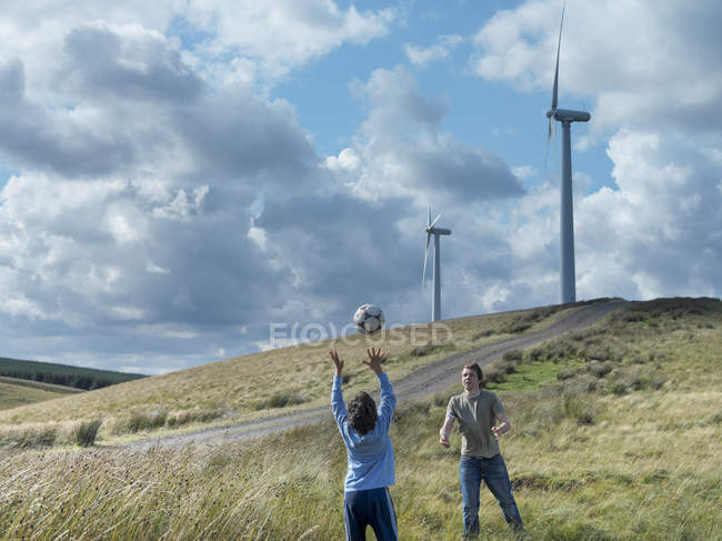Brothers throwing football to each other with windfarm in background — Stock Photo