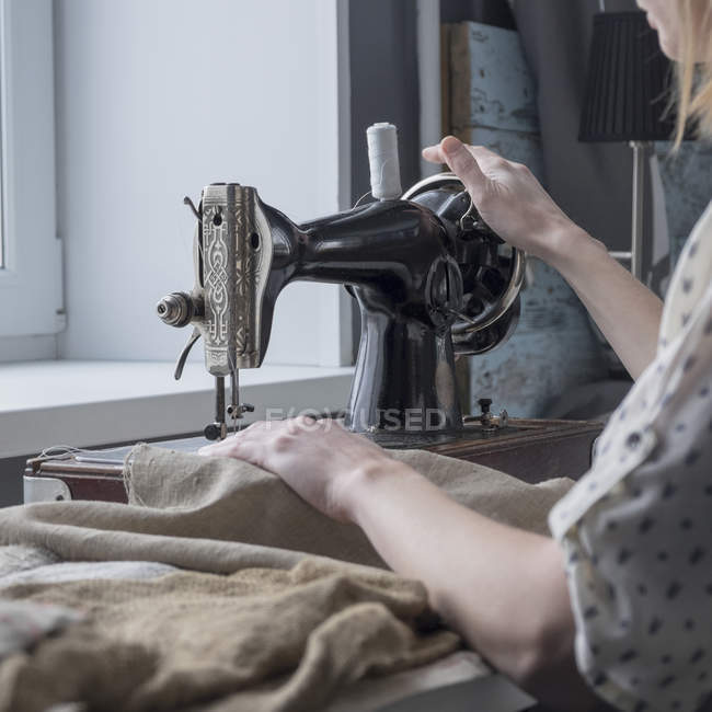 Close up of woman sewing textiles on vintage sewing machine — Stock Photo