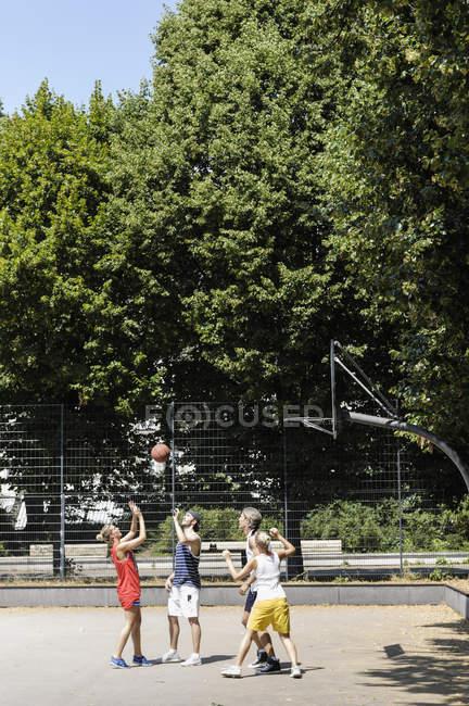Группа друзей, играющих в баскетбол в парке — стоковое фото
