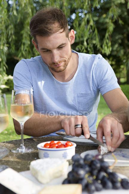 Homme adulte moyen assis à la table de pique-nique dans le jardin — Photo de stock