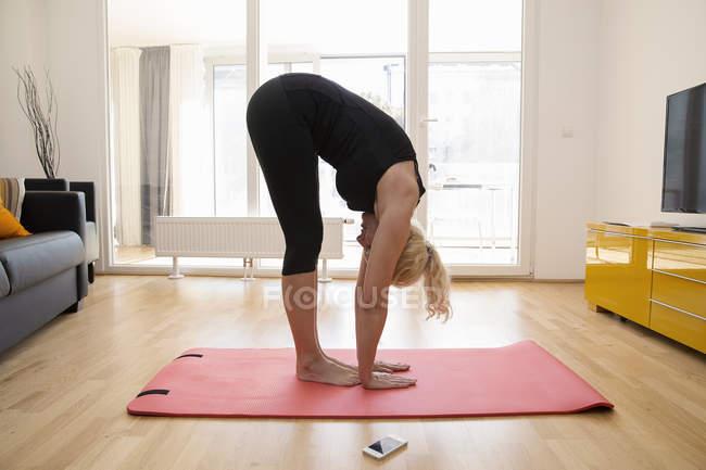 Вид сбоку зрелой женщины в петле на коврике для йоги, наклоняющейся над трогательным полом — стоковое фото