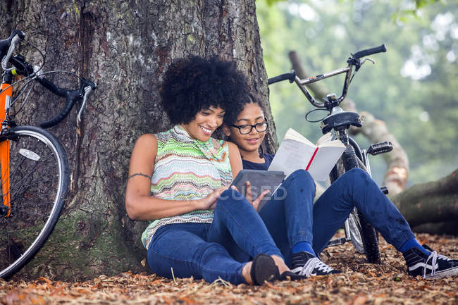 Mature woman and son sitting against park tree reading book and digital tablet — Stock Photo