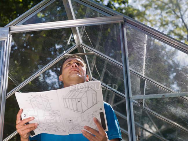 Mann mit Treibhausplänen im Garten — Stockfoto