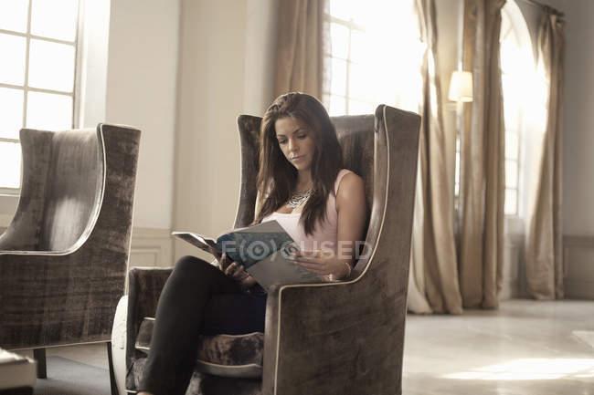 Mujer sentada en la silla leyendo revista - foto de stock
