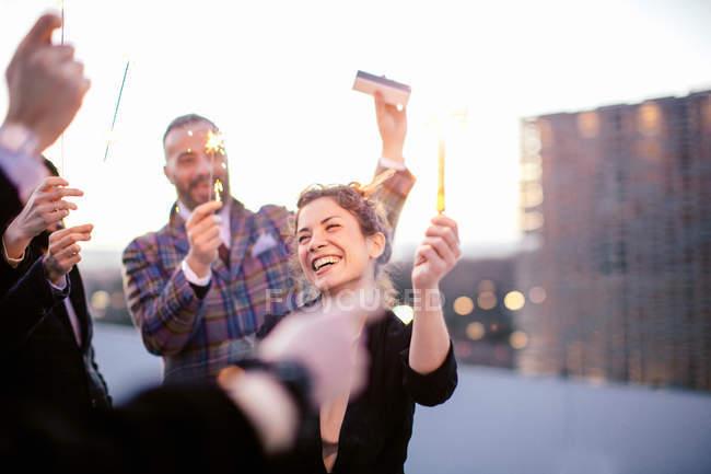 Gruppe von Freunden halten Funkeln auf Der Bank auf dem Dach — Stockfoto