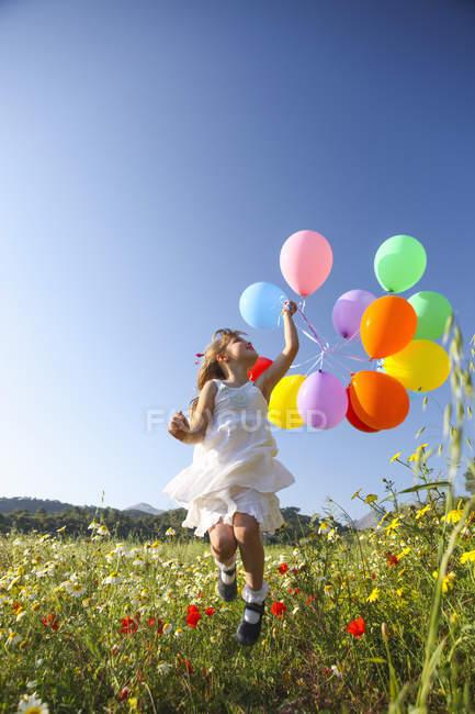 Menina pulando de alegria com balões coloridos no prado de flores silvestres, Maiorca, Espanha — Fotografia de Stock