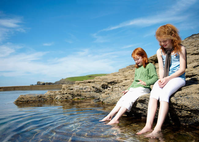 2 girls putting feet in rock pool — Stock Photo