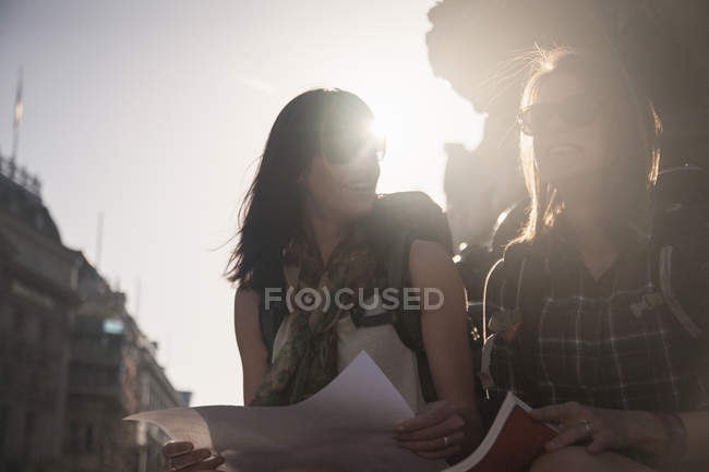 Women sitting at sunlight street with map and guidebook — стокове фото