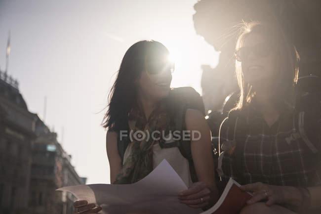 Жінки сидять на вулиці з картою та путівником. — стокове фото