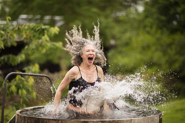 Mature woman splashing into fresh cold water tub at eco retreat — Stock Photo