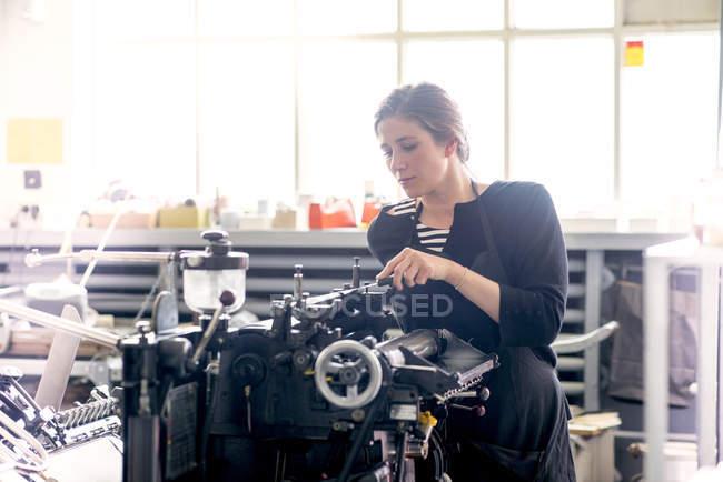 Imprimante de typographie femelle encrage impression machine en atelier — Photo de stock