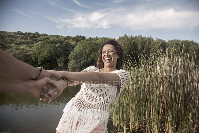 Молодая женщина у реки, взявшись за руки, склоняется обратно улыбается — стоковое фото