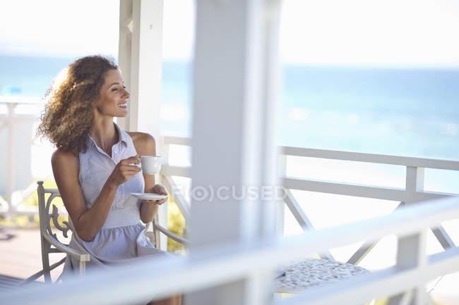 Junge Frau mit Kaffee blicken hinaus auf das Meer vom Strand Haus Balkon — Stockfoto