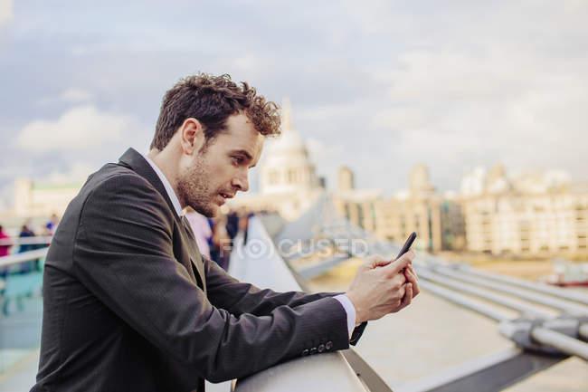Homme d'affaires lisant le message texte du smartphone tout en s'appuyant sur le pont Millennium, Londres, Royaume-Uni — Photo de stock