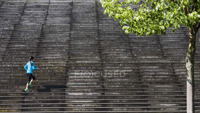 Vista distante de runner feminino na diagonal subindo escada de madeira — Fotografia de Stock