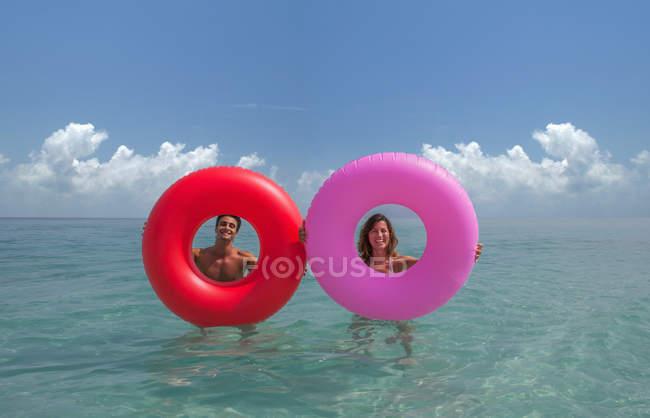 Пара, переглядаючи надувні кільця в море — стокове фото