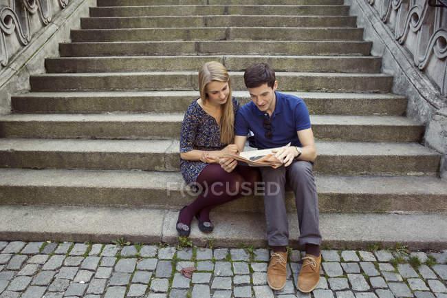 Giovane coppia seduta sulla vecchia scalinata di strada leggendo il giornale — Foto stock