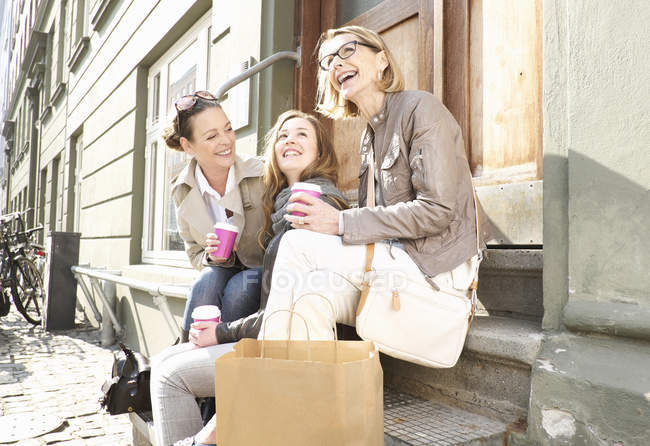 Three generation female family drinking takeaway coffee on street — Stock Photo