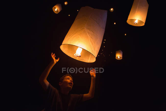 Portrait of boy releasing chinese lanterns on New Year's Eve, Krabi, Thailand, Southeast Asia — Stock Photo