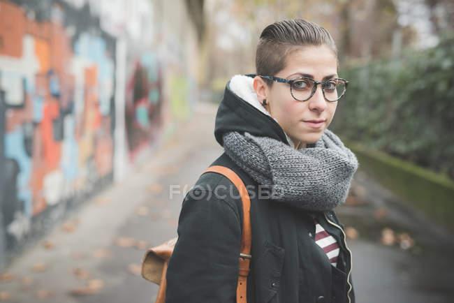 Adolescente en la calle, graffiti de la pared de fondo - foto de stock