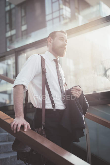 Stylish businessman carrying jacket moving down city stairway — Stock Photo
