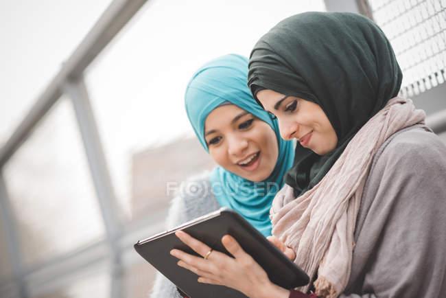 Dos mujeres jóvenes usando hiyabs usando tableta digital en la pasarela - foto de stock