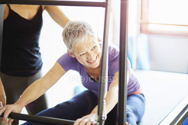 Mature woman and tutor practicing pilates on trapeze table in pilates gym — Stock Photo