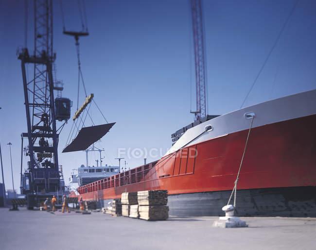 Estagiários que carregam aço no navio no porto — Fotografia de Stock
